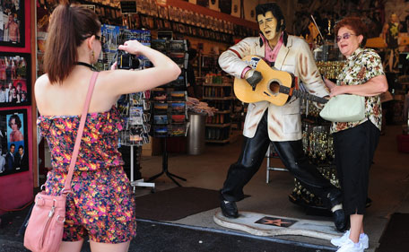 """A woman has her photo taken beside a life-sized model of the late Elvis Presley at a tourist gift-shop on the 34th anniversary of his death on August 16, 2011 in Hollywood, California. One of the most popular American singers of the 20th century, Elvis Aaron Presley was widely known by the single name """"Elvis"""" or simply """"the King"""", in reference to being annointed the """"King of Rock and Roll."""" (AFP)"""