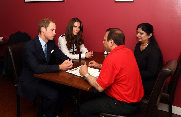 Britain's Prince William (L) and his wife Catherine, the Duchess of Cambridge, (2nd L) meet Ajay and Monika Bhatia at the Machan Express Coffee bar in the centre of Birmingham, which was ransacked during the recent riots in the area. (AFP)
