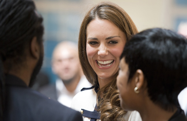 Britain's Catherine, the Duchess of Cambridge (Facing) talks with people as she and husband Prince William visit the Summerfield Community Centre, in Birmingham, central England, following riots in the area last week. (AFP)