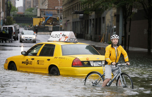 A bicyclist makes his way past a stranded taxi on a flooded New York City Street as Tropical Storm Irene passes through the city, Sunday, Aug. 28, 2011. Although downgraded from a hurricane to a tropical storm, Irene's torrential rain coupled with high winds and tides worked in concert to flood parts of the city. (AP)