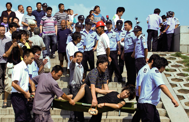 An injured woman is carried away after waves created by a tidal bore crash over a barrier on the Qiantang river at Haining, in east China's Zhejiang province. About 20 people were injured when they were caught too close to the river while viewing the annual tidal bore, which occurs when sea water from an unusually high tide funnels into the river, creating high waves. (AP)