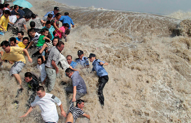 Policemen and residents run as waves from a tidal bore surge past a barrier on the banks of Qiantang River in Haining, Zhejiang province. As Typhoon Nanmadol approaches eastern China, the tides and waves in Qiantang River recorded its highest level in 10 years, local media reported. (REUTERS)