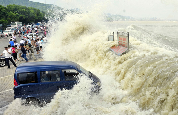 Spectators flee as waves created by a tidal bore crash over a barrier on the Qiantang river at Hangzhou, in east China's Zhejiang province. About 20 people were injured when they were caught too close to the river while viewing the annual tidal bore, which occurs when sea water from an unusually high tide funnels into the river, creating high waves. (AP)