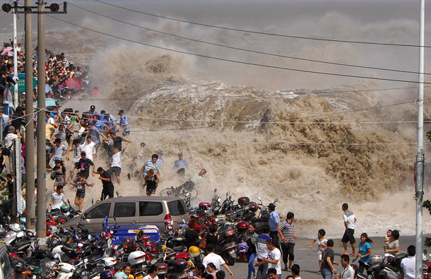 Spectators flee as waves created by a tidal bore crash over a barrier on the Qiantang river at Haining, in east China's Zhejiang province. About 20 people were injured when they were caught too close to the river while viewing the annual tidal bore, which occurs when sea water from an unusually high tide funnels into the river, creating high waves. (AP)