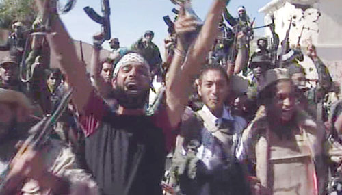 Libyan fighters celebrate in the streets of Sirte (AP)