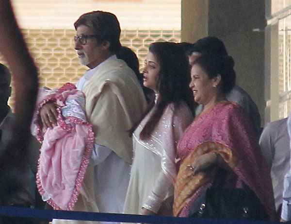 Amitabh Bachhan holds his granddaughter walking with Aishwarya Rai Bachhan as they leave the seven hills hospital in Mumbai on November 22, 2011 (AFP)