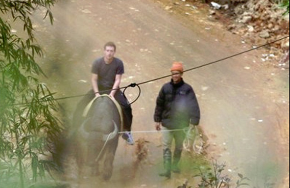 Facebook website founder Mark Zuckerberg rides a water buffalo in northern resort town of Sapa in Lao Cai province, Vietnam. (AP)