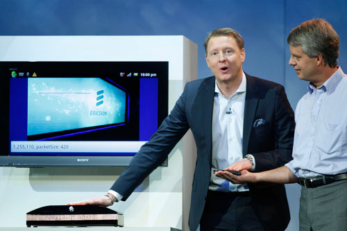 "Hans Vestberg (L), president and chief executive of the Ericsson Group, transfers a photo from a smartphone to a computer screen using his body during a keynote address at the 2012 International Consumer Electronics Show (CES) in Las Vegas, Nevada, January 11, 2012. Ericsson engineer Anders Stenkvist assists at right. Ericsson demonstrated the new technology, called ""capacitive coupling,"" in which the photograph was transferred from the phone, through the human body, to the screen without using radio signals (REUTERS)"