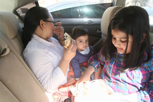 Residents of Al Bakar 'A' Tower have lunch in the car on Thursday noon (Chandra Balan)
