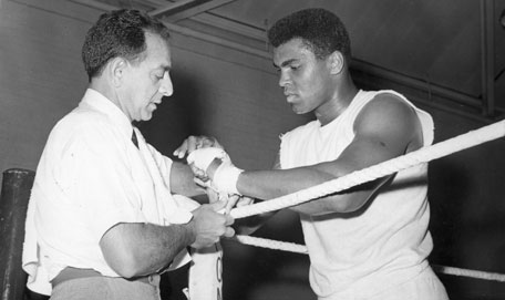 Muhammad Ali has his hands bandaged by his manager Angelo Dundee before a training session. (FILE)