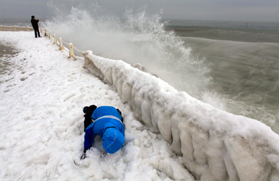 A child crouches as he protects himself from a wave on the shore of the Black Sea harbour of Constanta, 250 km (155 miles) east of Bucharest. (REUTERS)