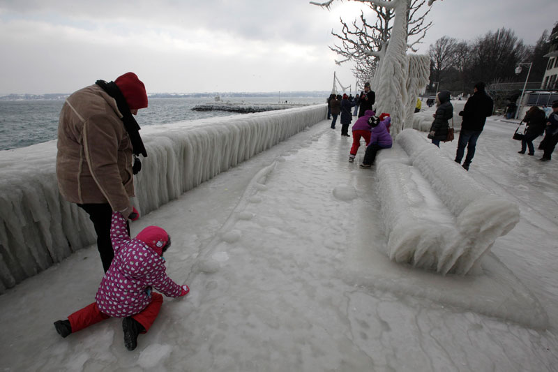 A man and a child walk along an ice covered promenade on the bank of Lake Leman in Versoix near Geneva on Sunday. Bitterly cold weather sweeping across Europe claimed more victims on Sunday and brought widespread disruption to transport services, with warnings that the chilling temperatures would remain into next week. (Reuters)