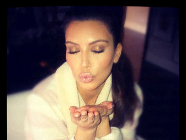 Kim Kardashian peck a kiss for followers on Twitter.
