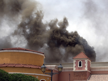 Smoke rises above the Villaggio Mall, in Doha's west end, as a fire took hold of the upscale mall in the Qatari capital of Doha Monday May 28, 2012. Qatar's Interior Ministry said 13 children were among 19 people killed in a fire that broke out at one of the Gulf state's fanciest shopping mall on Monday. The Villaggio opened in 2006 and is one of Qatar's most popular shopping and amusement destinations. It includes an ice skating rink and indoor Venice-style gondola rides. (AP)