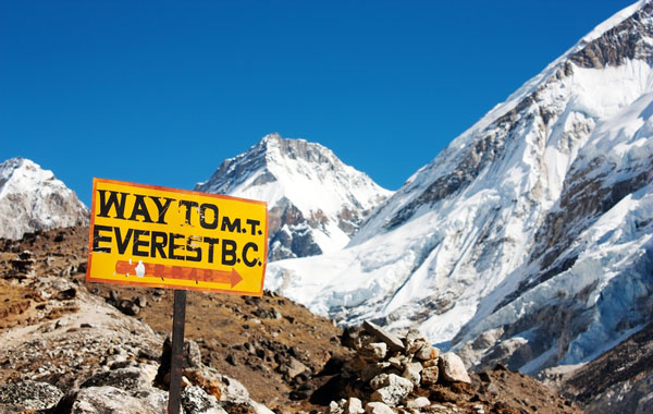 Signpost way to mount everest b.c. and himalayan panorama. [Image via Shutterstock]