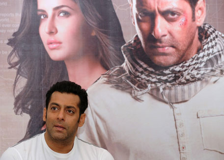 Bollywood actor Salman Khan smiles as he stands in front of a poster showing himself and actress Katrina Kaif at a press conference to promote the film 'Ek Tha Tiger' or 'Once There was a Tiger'. (AFP)
