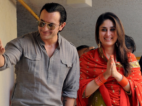Newly-wedded Bollywood personalities Saif Ali Khan (L) and Kareena Kapoor gesture as they pose for the media outside Khan's residence in Mumbai on October 16, 2012. (AFP)