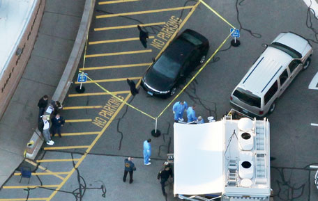 Responders gather at the scene of a mass shooting at Sandy Hook Elementary School with police tape surrounding a vehicle on December 14, 2012 in Newtown, Connecticut. Twenty-seven are dead, including 20 children, after a gunman identified as Adam Lanza in news reports, opened fire in the school. Lanza also reportedly died at the scene. (Getty Images/AFP)