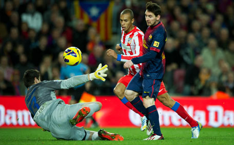 Lionel Messi (right) of Barcelona scores his side's fourth goal against Atletico de Madrid during the la Liga match at the Camp Nou stadium on December 16, 2012 in Barcelona, Spain. (GETTY)