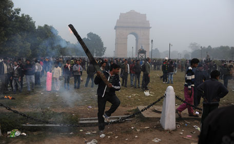 An Indian demonstrator holds up a burning plank, part of a barricade, during a protest calling for  better safety for women following the rape of a student last week, in front the India Gate monument in New Delhi on December 23, 2012. In the biggest protest so far, several thousand college students rallied at the India Gate monument in the heart of the capital where they were baton-charged, water cannoned and tear gassed by the police. (AFP)