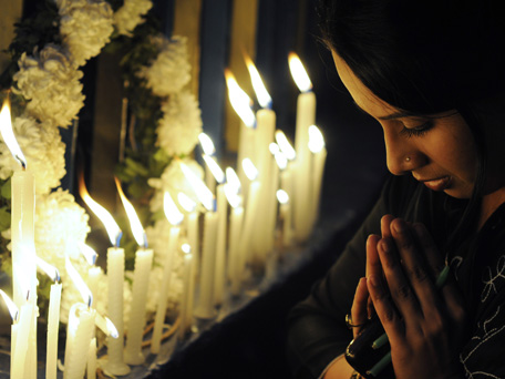 An Indian activist prays as she takes part in a candlelight vigil in Kolkata on December 30, 2012, after the cremation ceremony for a gangrape victim. The victim of a gang-rape and murder which triggered an outpouring of grief and anger across India was cremated at a private ceremony, hours after her body was flown home from Singapore. A student of 23-year-old, the focus of nationwide protests since she was brutally attacked on a bus in New Delhi two weeks ago, was cremated away from the public glare at the request of her traumatised parents.  (AFP)