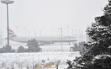A British Airways plane drives on the snow covered tarmac of Roissy Charles-de-Gaulle airport, outside Paris. Air France cancelled 40 percent of its short- and medium-haul flights from Paris airports on Sunday as heavy snow disrupted air, road and rail transportation for a second day. (AFP)