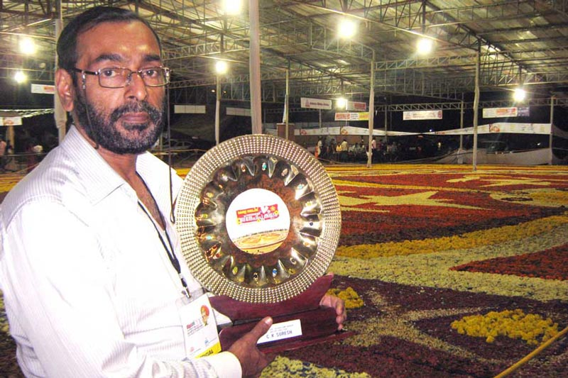 Cinema art director C K Suresh with the Limca Award. The world's biggest 'rangoli' created by him is seen in the background.