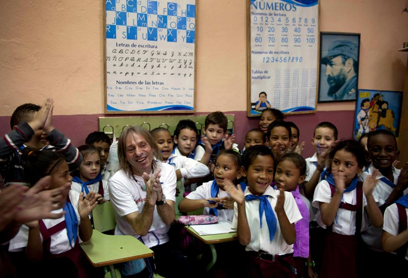 Schoolchildren pose for photos with French daredevil Alain Robert after he climbed the exterior their Angela Landa elementary school building without using ropes or a safety net in Old Havana, Cuba on Tuesday, February 5.  (AP)