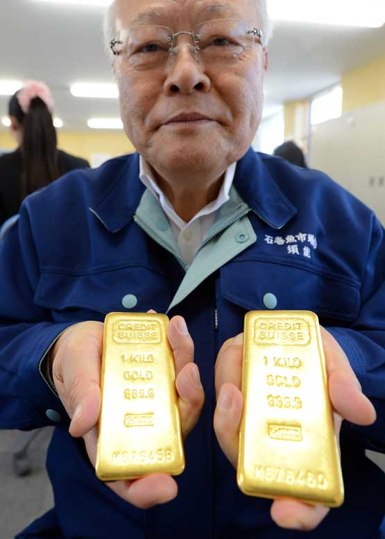 Kunio Sunow shows off slabs of gold at his office. (AFP)