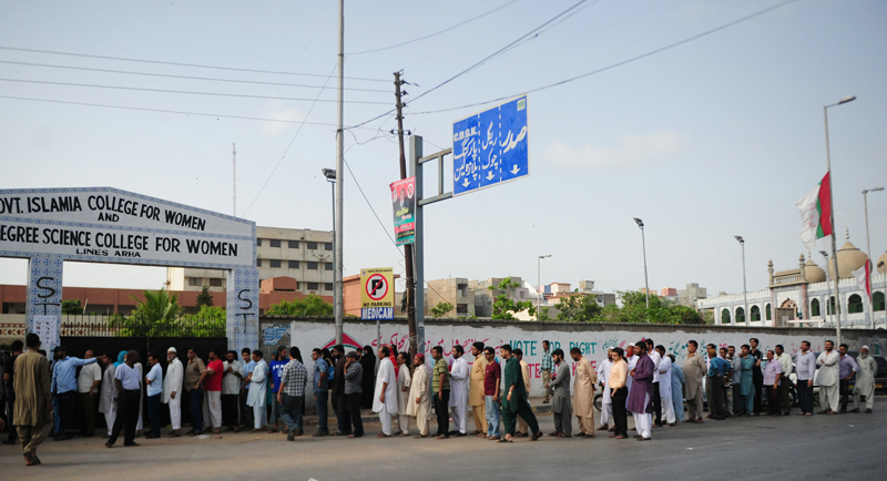 Pakistani voters queue for their turn to cast their vote outside a polling station in Karachi on May 11, 2013. (AFP)