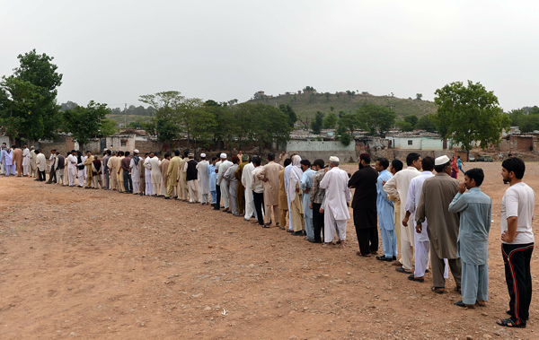 Pakistani voters stand in a queue waiting for their turn outside a polling station in Islamabad on May 11, 2013. (AFP)