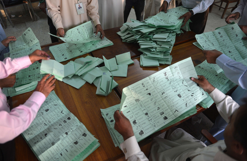 """Pakistani election officials count ballot papers at the end of polling in Islamabad on May 11, 2013. Polling stations closed at 6:00 pm (1300 GMT) in Pakistan's historic general elections, which saw a """"huge"""" turnout in the largest province of Punjab, an election commission official announced. (AFP)"""