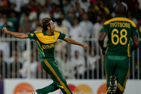 South African bowler Imran Tahir (left) celebrates after taking a wicket of Pakistan's cricketer Wahab Riaz in Sharjah Cricket Stadium in Sharjah on October 30, 2013. (AFP)