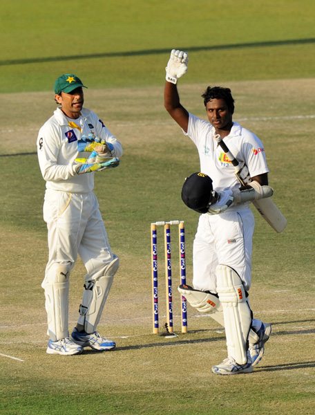 Sri Lankan cricket captain Angelo Mathews (R) celebrates his century as Pakistan wicketkeeper Younis Khan looks on during the fourth day of the first cricket Test match between Pakistan and Sri Lanka at the Sheikh Zayed Stadium in Abu Dhabi on January 3, 2014. (AFP)