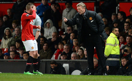 Manchester United manager David Moyes (R) speaks to Manchester United's Dutch defender Alexander Büttner during the English FA Cup third round football match between Manchester United and Swansea City at Old Trafford in Manchester, northwest England, on January 5, 2014. Swansea won 2-1. (AFP)