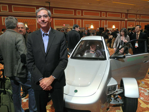 Paul Elio, founder and CEO of Elio Motors poses in front of a prototype of three-wheeled car on display at the at the Showstoppers startup showcase on the sidelines of the 2014 Consumer Electronics Show(CES) January 9, 2014 in Las Vegas, Nevada. (AFP)
