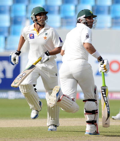 Misbah ul Haq and Younis Khan run between wickets on day three of the second Test between Pakistan and Sri Lanka at Dubai International Stadium on January 10, 2014. (KAMAL JAYAMANNE)