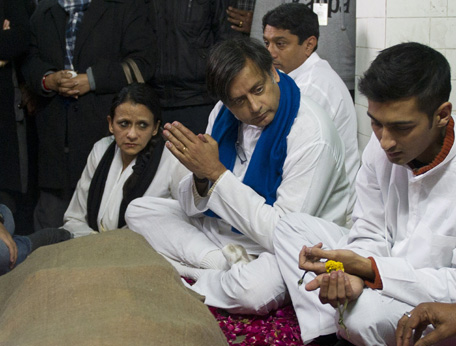 "India's Human Resources Minister Shashi Tharoor (C) sits with other relatives and friends alongside the body of his wife Sunanda Pushkar at a cremation centre in New Delhi on January 18, 2014. The wife of Indian minister Shashi Tharoor, found dead in a luxury hotel after accusing her husband of being unfaithful, suffered an ""unnatural, sudden death"", a doctor who performed an autopsy on her body said. (AFP)"