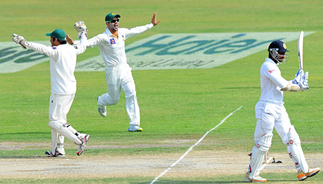 Pakistan wicketkeeper Sarfraz Ahmed (L) and Ahmed Shehzad (C) celebrate the dismissal of Sri Lankan batsman Kumar Sangakkara during the fourth day of the third and final cricket Test match between Pakistan and Sri Lanka at the Sharjah International Cricket Stadium, in the Gulf emirate of Sharjah, on January 19, 2014. (AFP)