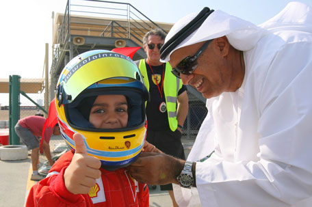 Rashid Al Dhaheri gets his helmet secured by his father Ali before a race at the Kartdrome. (SUPPLIED)