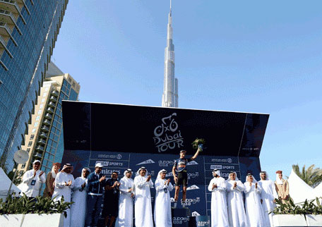 US cyclist Taylor Phinney of BMC Racing Team celebrates on the podium near in front of the Burj Khalifa, the world's talled tower on February 8, 2014 in Dubai. (AFP)