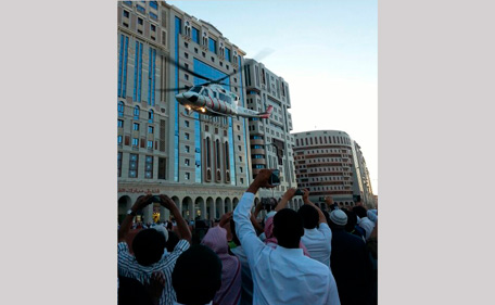 Crowd take pictures of a helicopter evacuating people from a hotel after a fire broke out, in Medina February 8, 2014. Fifteen people died and around 130 were injured when a fire broke out in a hotel packed with Muslim pilgrims in the Saudi Arabian city of Medina on Saturday, the state news agency said. (REUTERS)