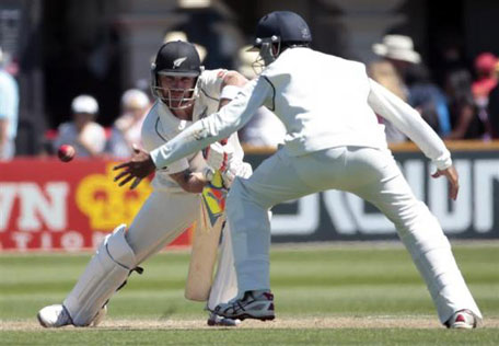 India's Cheteshwar Pujara (right) fields a shot from New Zealand's Brendon McCullum during the second innings on day three of the second Test at the Basin Reserve in Wellington, February 16, 2014. (REUTERS)