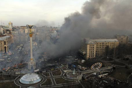 Smoke rises above Independence Square during anti-government protests in central Kiev in the early hours. (REUTERS)