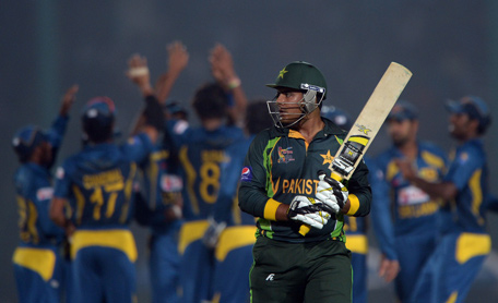 Pakistani cricketer Sharjeel Khan reacts after being given out as Sri Lankan cricketers celebrate his wicket during the opening match of the Asia Cup one-day tournament between Pakistan and Sri Lanka at the Khan Shaheb Osman Ali Stadium in Fatullah, on the outskirts of Dhaka on February 25, 2014. (AFP)