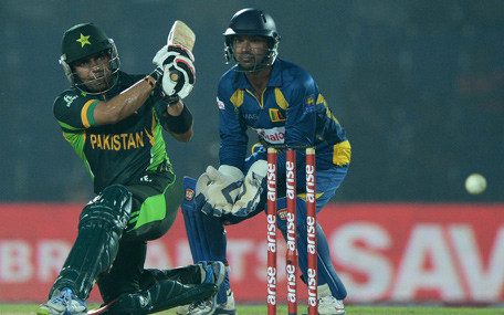 Pakistan cricketer Umar Akmal (L) plays a shot as Sri Lankan wicketkeeper Kumar Sangakkara looks on looks on during the opening match of the Asia Cup one-day cricket tournament between Pakistan and Sri Lanka at the Khan Shaheb Osman Ali Stadium in Fatullah, on the outskirts of Dhaka on February 25, 2014. (AFP)