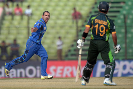 Afghan cricketer Samiullah Shenwari (left) celebrates after taking the wicket of Pakistani batsman Ahmed Shehzad during the third match of the Asia Cup one-day cricket tournament at the Khan Shaheb Osman Ali Stadium in Fatullah, Dhaka on February 27, 2014. (AFP)