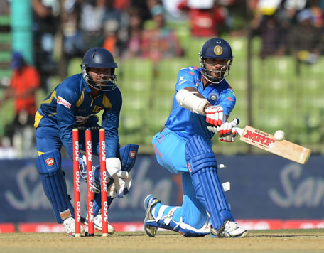 India's Shikhar Dhawan sweeps during Match four of the Asia Cup one-day international cricket tournament between India and Sri Lanka at Fatullah, Dhaka on February 28, 2014. (AFP)