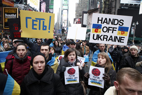 People take part during a protest in Times Square against Russian military intervention in the Crimea region of Ukraine, on March 2, 2014, in New York City. Interim Ukrainian Prime Minister Arseniy Yatsenyuk urged Russian President Vladimir Putin to pull back troops that spread out across the Crimean Peninsula today, one day after Russia's parliament approved to use military force in Ukraine.(AFP)