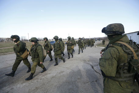 Military personnel, believed to be Russian servicemen, walk outside the territory of a Ukrainian military unit in the village of Perevalnoye outside Simferopol March 3, 2014. Ukraine mobilised for war on Sunday and Washington threatened to isolate Russia economically after President Vladimir Putin declared he had the right to invade his neighbour in Moscow's biggest confrontation with the West since the Cold War. Russian forces have already bloodlessly seized Crimea, an isolated Black Sea peninsula where Moscow has a naval base. (REUTERS)